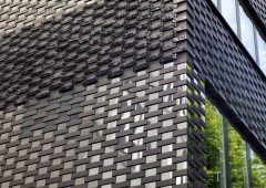Dramatic black façade with custom glazed bricks